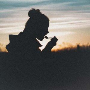 Silhouette Person isst bei Sonnenuntergang
